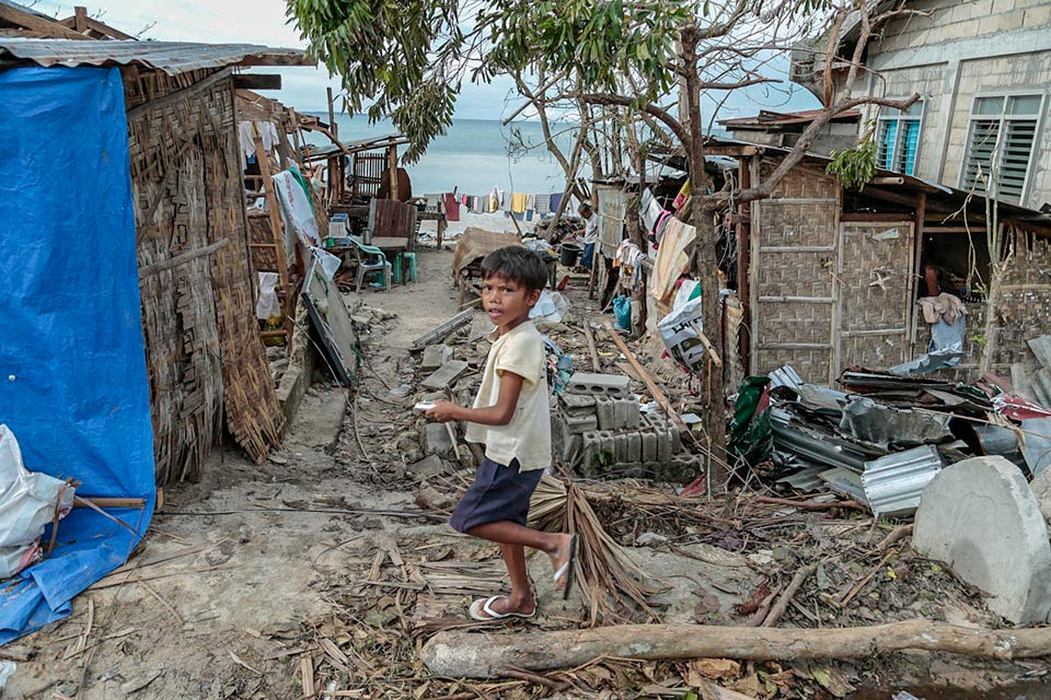 Child standing at destruction caused by Typhoon Haiyan, Philippines
